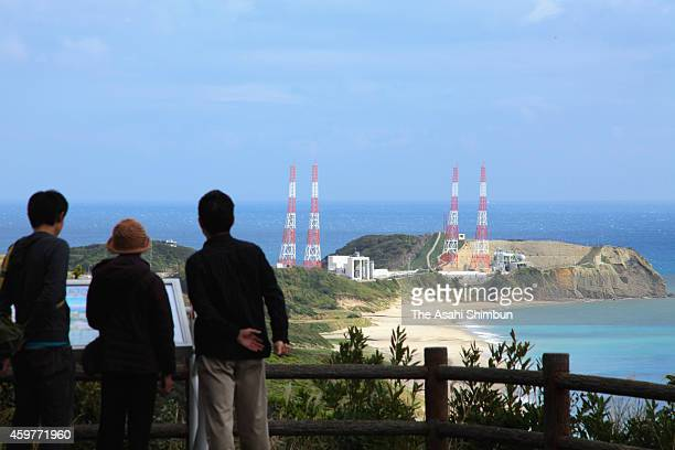 Visitors to the Tanegashima Space Center gaze at the launch pad where the H2A rocket carrying the Hayabusa 2 asteroid explorer was scheduled to be...