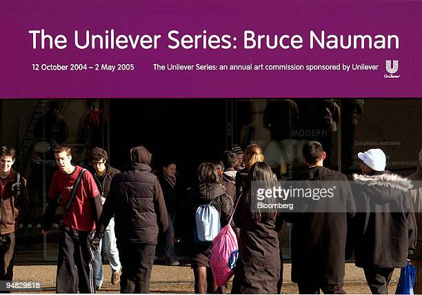 Visitors to the Tate Modern in London UK walk under a sign advertising an exhibition titled The Unilever Series Bruce Nauman' on February 22 2005...