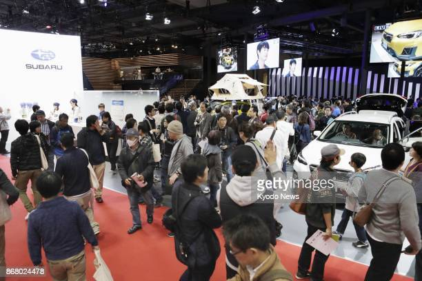 Visitors to the Tokyo Motor Show gather in the Subaru booth on Oct 28 at Tokyo Big Sight Automakers are promoting AI and electric vehicles at the...