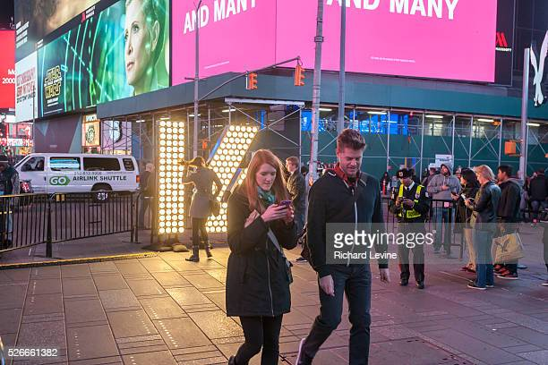 """Visitors to Times Square in New York pose in front of the two seven-foot-tall numerals """"1"""" and """"6"""" on Tuesday, December 15, 2015 . The """"16"""" will be..."""