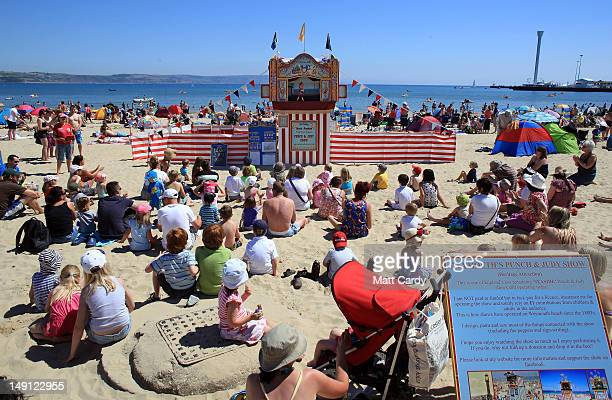 Visitors to Weymouth beach spend time in the sunny weather as they watch a punch and judy performer on July 23 2012 in Weymouth England After weeks...