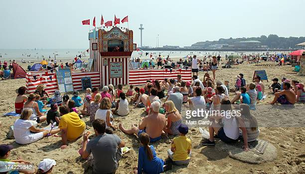 Visitors to Weymouth watch a traditional punch and judy show on the beach on July 22 2013 in Weymouth England According to forecasters the current...