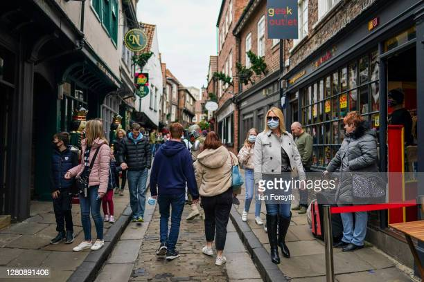 Visitors to York walk through the famous Shambles street on October 18, 2020 in York, England. York city has become another of England's high risk...