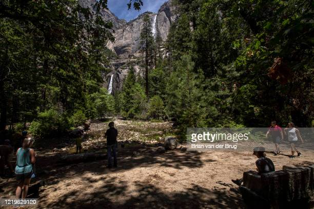 Visitors to Yosemite Valley take in the vistas of Yosemite Falls for the first time in 2½ months after closing because of the coronavirus on...