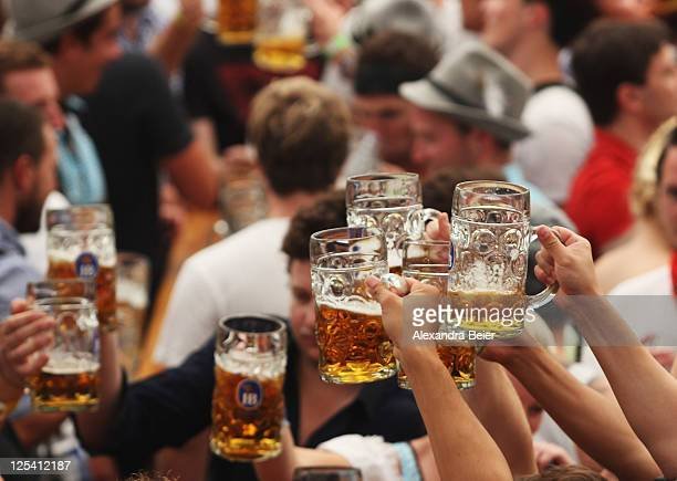 Visitors toast with beer mugs during the opening day of the Oktoberfest 2011 beer festival at Theresienwiese on September 17 2011 in Munich Germany