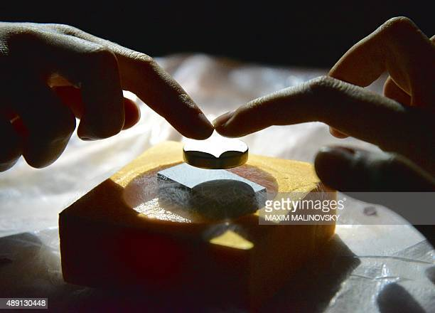 Visitors touch a superconducting magnet at the Elemento Science Museum in Minsk on September 19 2015 The superconducting element is cooled by liquid...