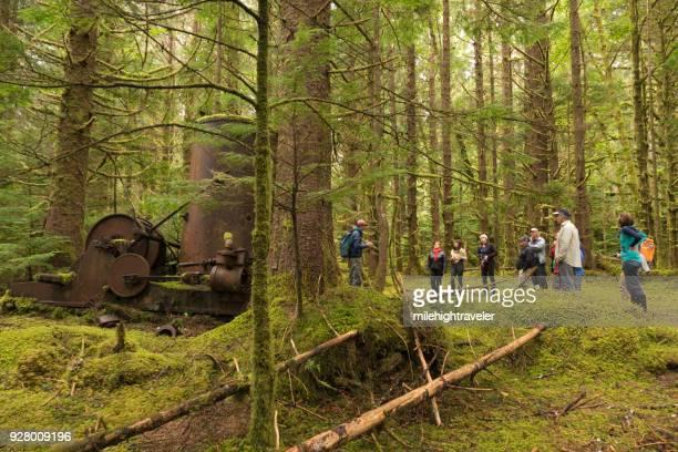 Visitors tourist explore hike Louise Island mossy logging equipment Haida Gwaii British Columbia Canada