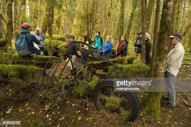 Visitors tourist explore hike Louise Island mossy logging equipment Haida Gwaii British Columbia Canada