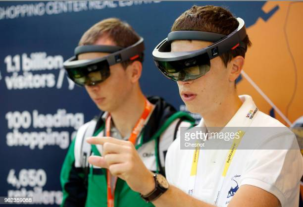 Visitors try a virtual reality headmounted headset Microsoft HoloLens during the Viva Technology show at Parc des Expositions Porte de Versailles on...