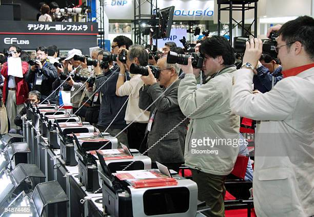 Visitors try out Canon Inc's EOS digital cameras at the Photo Imaging Expo 2008 in Tokyo Japan on Wednesday March 19 2008 Japan's electronics makers...