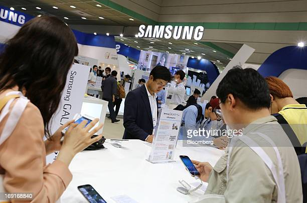 Visitors try out Samsung Electronics Co. Galaxy S4 smartphones at the World IT Show 2013 in Seoul, South Korea, on Tuesday, May 21, 2013. The IT show...