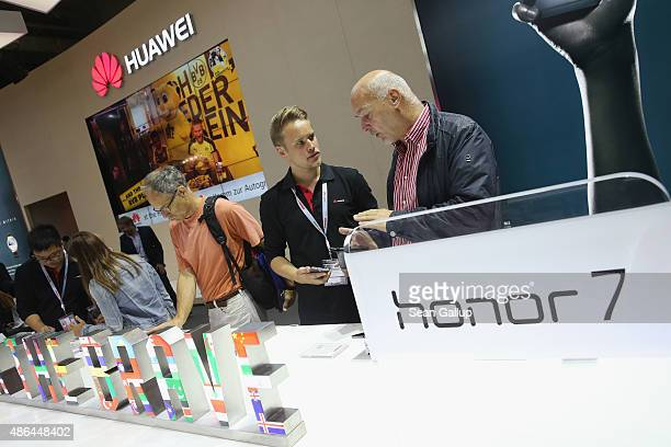 Visitors try out the Honor 7 smartphone at the Huawei stand at the 2015 IFA consumer electronics and appliances trade fair on September 4, 2015 in...