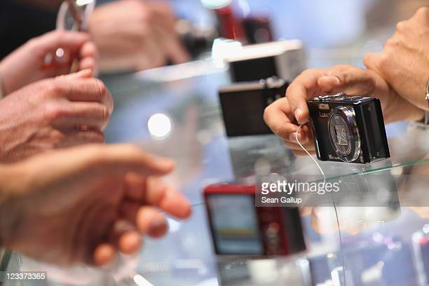 Visitors try out the latest point and shoot digital cameras at the Panasonic stand at the IFA 2011 consumer electonics and appliances trade fair on...