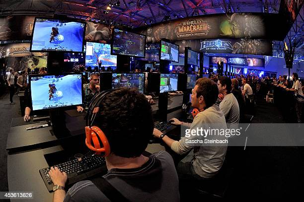 Visitors try out the massively multiplayer online role-playing game 'World Of Warcraft' at the Blizzard Entertainment stand at the 2014 Gamescom...