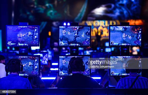 Visitors try out the massively multiplayer online role-playing game 'World Of Warcraft' at the Blizzard Entertainment stand at the Gamescom 2015...