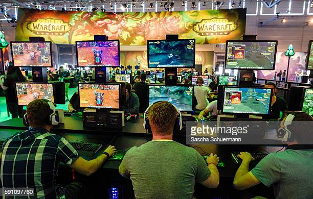 Visitors try out the massively multiplayer online role-playing game 'World Of Warcraft' at the Blizzard Entertainment stand at the Gamescom 2016...