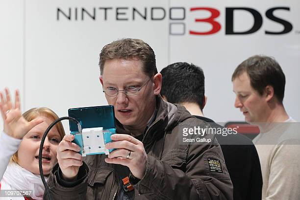 Visitors try out the new Nintendo 3DS handheld gaming device with a 3D display at the Nintendo DS stand at the CeBIT technology trade fair on March 2...
