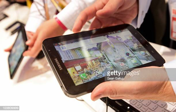 Visitors try out the new Samsung Galaxy Tab a product that has features and looks similar to the Apple iPad at the Samsung stand at the 2010 IFA...