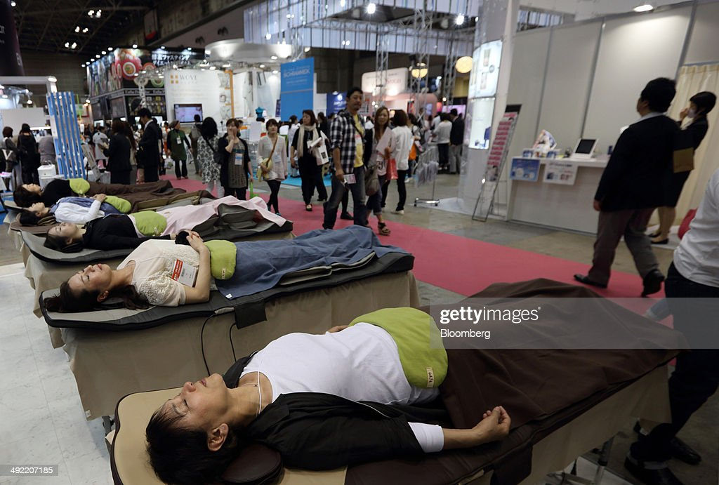 Visitors try stretching machines at the Beautyworld Japan fair in Tokyo, Japan, on Monday, May 19, 2014. The business-to-business trade fair hosted by Messe Frankfurt is held through May 21. Photographer: Tomohiro Ohsumi/Bloomberg via Getty Images