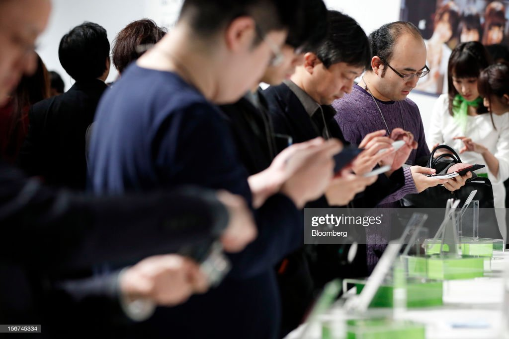 Visitors try the HTC J Butterfly smartphone, produced by HTC.Corp. during the unveiling event in Tokyo, Japan, on Tuesday, Nov. 20, 2012. Taiwan's HTC Corp. needs to improve its global brand awareness to gain share in China, and its newly unveiled model is likely to help the vendor do that. Photographer: Kiyoshi Ota/Bloomberg via Getty Images