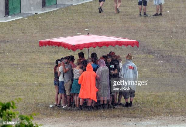Visitors try to cover from heavy rain during the 'Rock Im Park' music festival at Zeppelinfeld on June 3 2017 in Nuremberg Germany