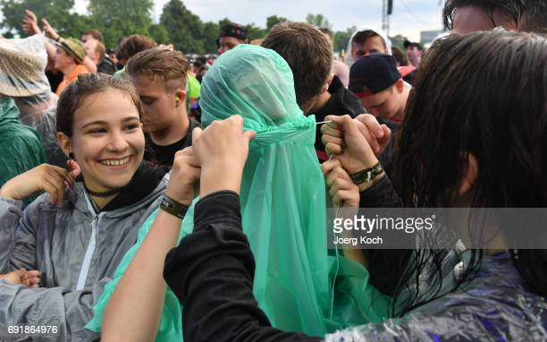 Visitors try to cover from starting heavy rain during the 'Rock Im Park' music festival at Zeppelinfeld on June 3 2017 in Nuremberg Germany