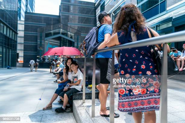 Visitors try to remain cool while waiting in line at the Liberty One Observation Deck in sweltering heat on July 1 2018 in Philadelphia Pennsylvania...