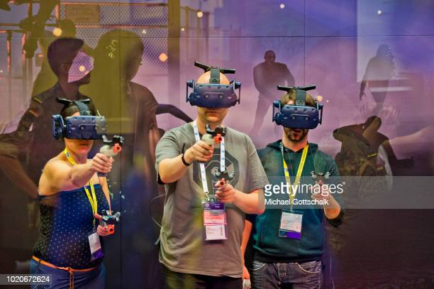 A young boy tries a video game on a super ultra wide videoscreen at 2018 gamescom fair press day on August 21 2018 in Cologne Germany Gamescom is...