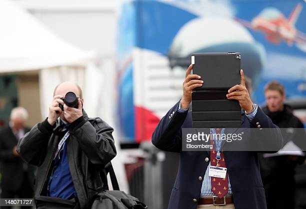 Visitors use a camera left and an Apple Inc ipad to photograph an Airbus SAS A380 during a flypast on the first day of the Farnborough International...