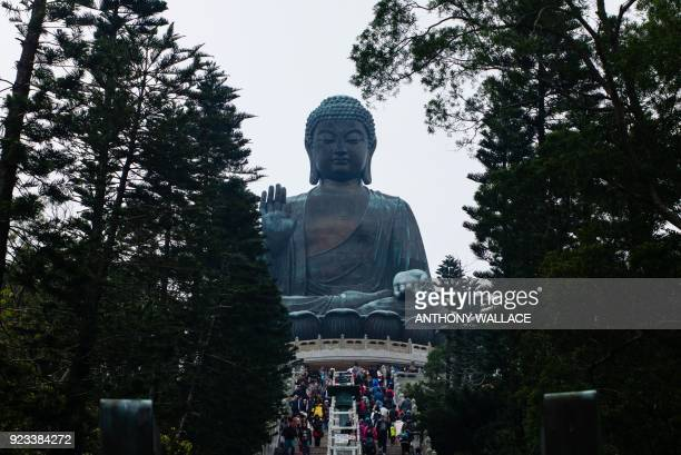 Visitors use a stairway that leads to the Big Buddha on Hong Kong's outlying Lantau Island on February 23, 2018. / AFP PHOTO / ANTHONY WALLACE