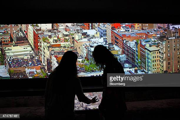Visitors use an interactive wall monitor displaying a city skyline inside the SAP AG Inspiration Pavilion at the company's headquarters in Walldorf...