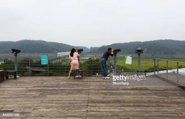 Visitors use binoculars to look across to the north side of the border at the Imjingak pavilion near the Demilitarized Zone in Paju South Korea on...