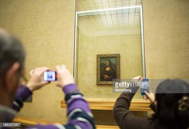 Visitors use mobile handsets to photograph the Mona Lisa painting at the Louvre museum in Paris France on Monday March 22 2013 Jobless claims have...