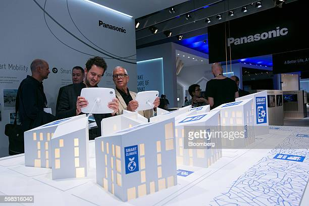 Visitors use tablet devices to interact with a Smart City prototype model on the Panasonic Corp exhibition stand during the IFA International...