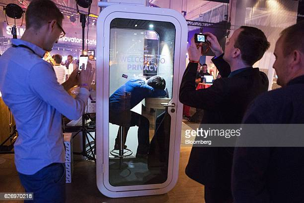 Visitors use their smartphone devices to take photographs of an attendee taking a nap in a privacy booth during the Slush startups event in Helsinki,...