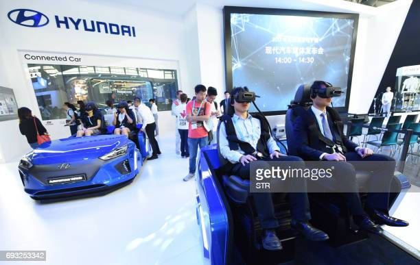 Visitors use virtual reality headsets on the the Hyundai stand on the opening day of the Consumer Electronics Show Asia in Shanghai on June 7 2017...