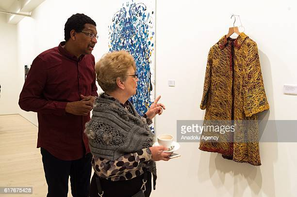 Visitors view a jacket donated by her Royal Highness Sheikha Jawaher Bint Mohammed Al Qasimi have been painted by artist Johny Dar in aid of the...