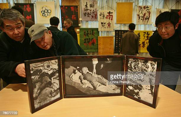 Visitors view a mini folding screen named Mourning Nanjing by artist Alex Rudinskyde of the USA during a calligraphy exhibition to mark the 70th...