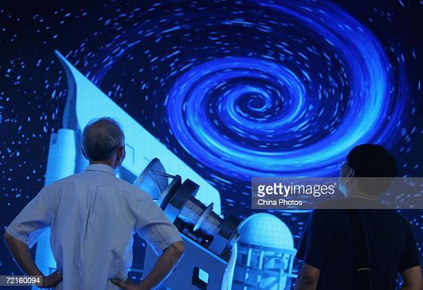 Visitors view a model of the large sky area multiobject fiber spectroscopic telescope with the outer space image in the background during 8th China...