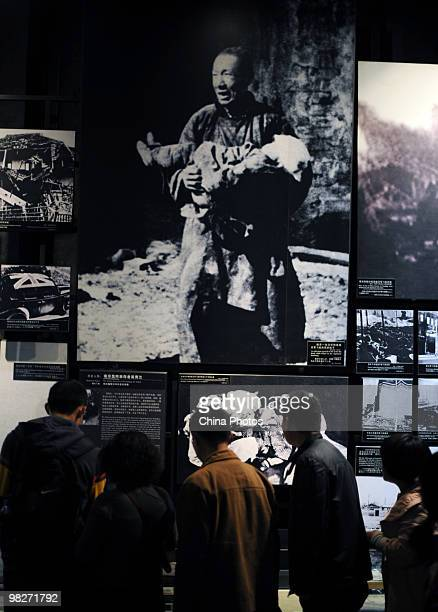 Visitors view documents at the Memorial Hall of the Victims in the Nanjing Massacre as tens of thousands of people come to mourn victims a day before...