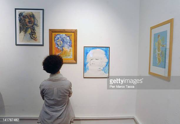 Visitors view paintings displayed at Lazzi sberleffi dipinti at Palazzo Reale on March 23 2012 in Milan Italy