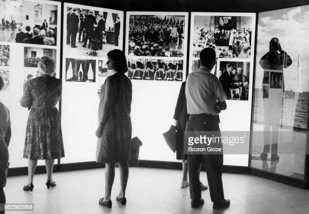 Visitors view photographs at the traveling John F Kennedy Library Exhibit at the Museum of Fine Arts in Boston on Aug 19 1964