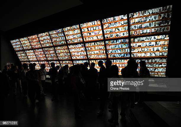 Visitors view photos of massacre survivals at the Memorial Hall of the Victims in the Nanjing Massacre as tens of thousands of people come to mourn...