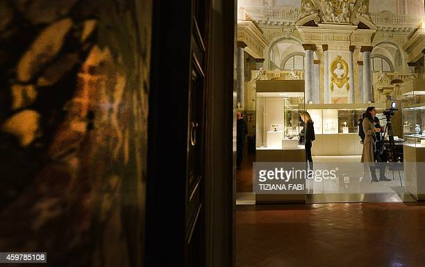 Visitors view pieces on display during the opening of the exhibition I tesori della fondazione Buccellati at Palazzo Pitti in Florence on December 1...