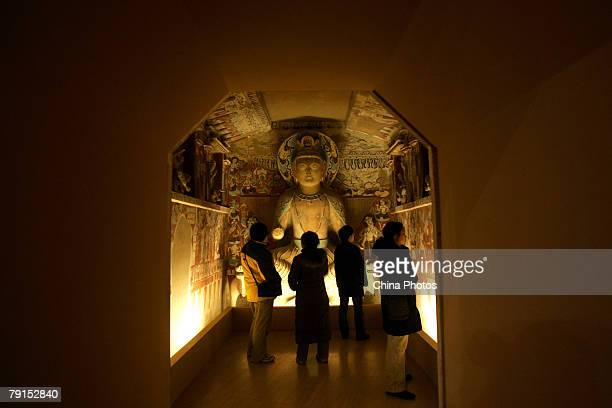 Visitors view replica of parts of the Mogao Cave during the Dunhuang Art Exhibition at the National Art Museum of China on January 21, 2008 in...
