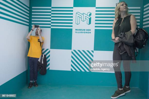 Visitors view the Ames Room an exhibition part of the Museum of Illusions in Vienna Austria on October 16 2017 The Museum of Illusions bring a...