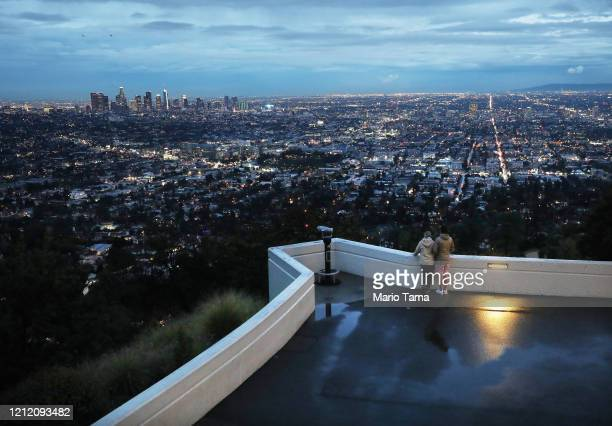 Visitors view the city skyline at dusk from a terrace at the Griffith Observatory which will be closed starting tomorrow due to the spread of the...