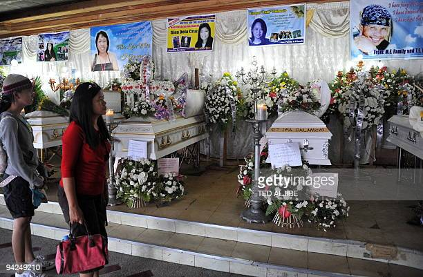 Visitors view the coffins of slain journalists during the wake at a funeral home in General Santos City South Cotabato on November 30 2009 A...
