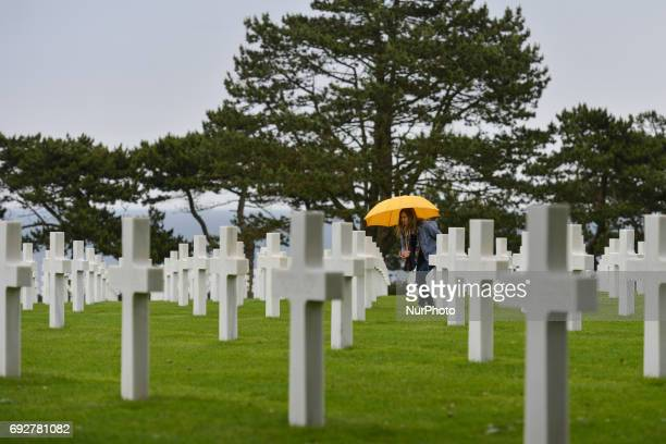 Visitors view the graves of fallen soldiers at the Normandy American Cemetery that contains the remains of 9,387 American military dead, most of whom...