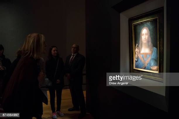 Visitors view the painting 'Salvator Mundi' by Leonardo da Vinci at Christie's New York Auction House November 15 2017 in New York City The coveted...